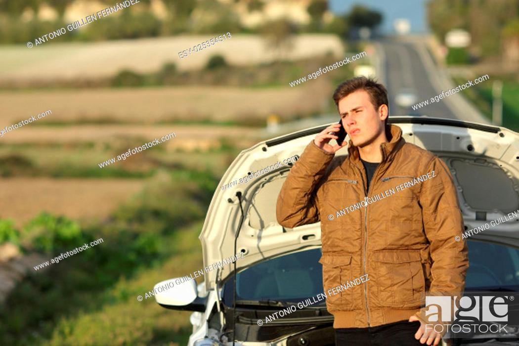 Stock Photo: Guy calling roadside assistance for his breakdown car i a country road.