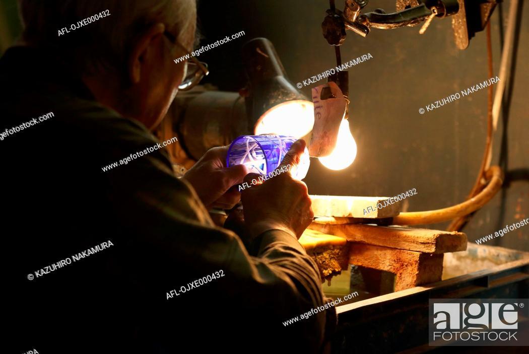 Stock Photo: Edo Kiriko traditional Japanese glassware artisan working in the studio.