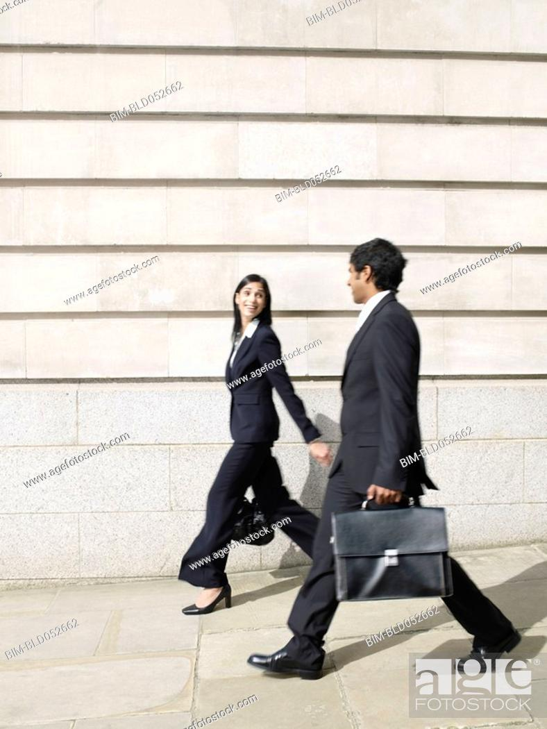 Stock Photo: Multi-ethnic businesspeople walking on sidewalk.