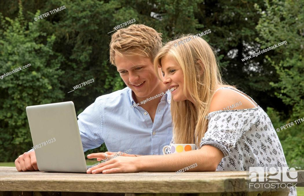 Stock Photo: Teenage couple using a computer on a garden table.