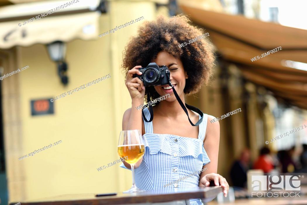 Stock Photo: Young woman taking photo with camera outdoors.