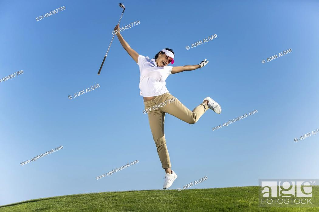 Stock Photo: Bright excited brunette in sportswear jumping happily with golf driver in hands above green lawn on blue sky.
