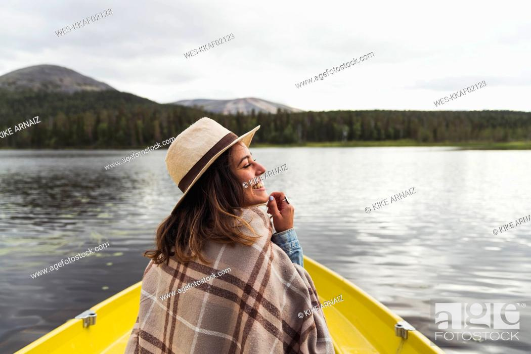 Stock Photo: Finland, Lapland, happy woman wearing a hat on a boat on a lake.