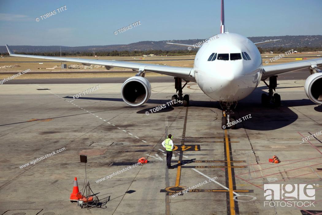 Stock Photo: Ground crew and jet on runway.