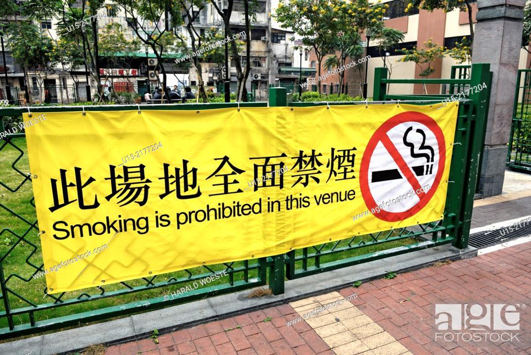 """Stock Photo: Hong Kong, China, Asia. Hong Kong Kowloon. Large yellow bilingual banner in english and chinese at the entrance to a small urban park advising that """"""""Smoking is."""