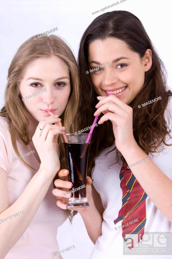 Stock Photo: Two young women sharing a glass of drink.
