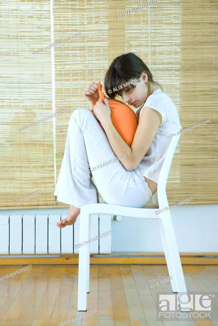 Young Woman Sitting On Chair With Knees Up Holding Cushion Stock