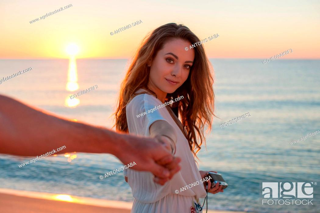 Stock Photo: Young woman holding boyfriends hand at sunset on beach, Castiadas, Sardinia, Italy.