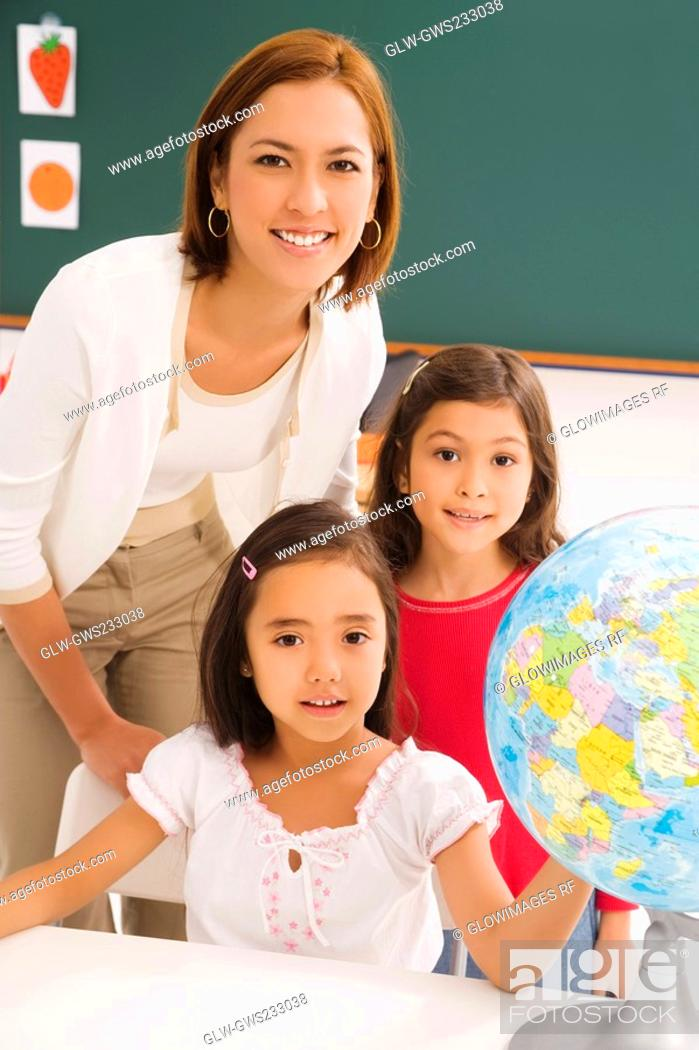 Stock Photo: Portrait of two schoolgirls with her female teacher in a classroom.