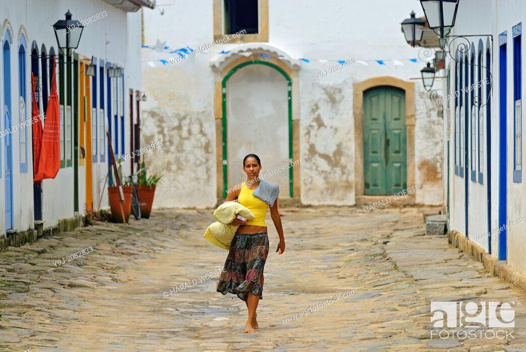 Stock Photo: Local brazilian woman walking through the historic center; Paraty, Espirito Santo, Brazil. The beautiful colonial town of Paraty has been a UNESCO World.