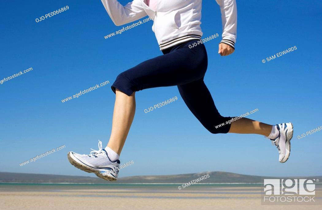 Stock Photo: Woman running on beach.