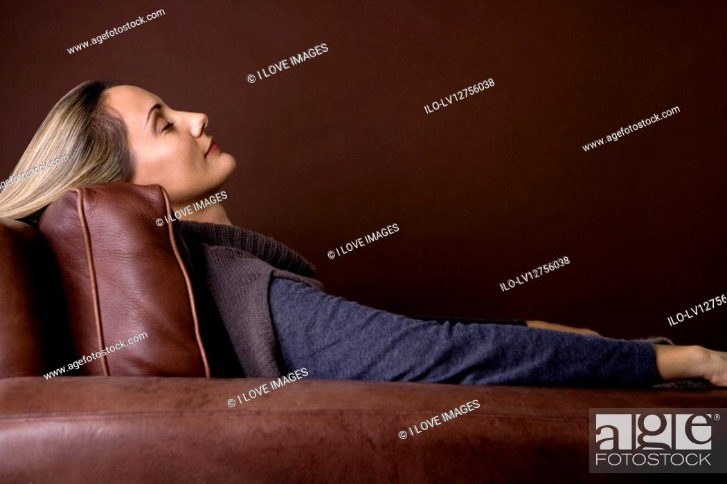 Stock Photo: A mid adult woman resting in an armchair.
