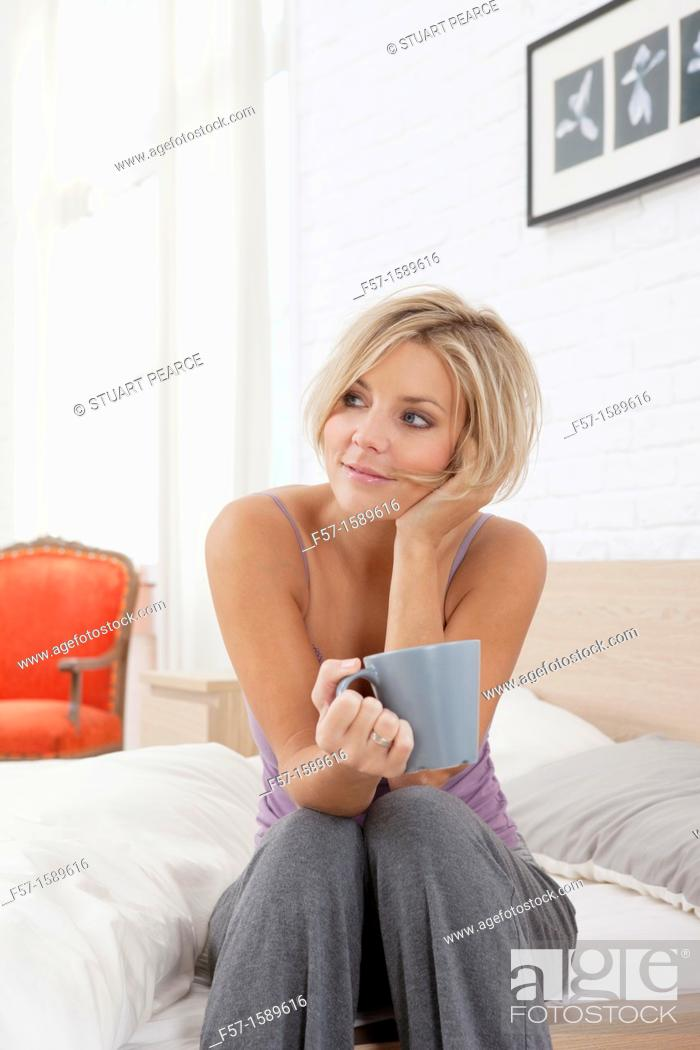 Stock Photo: Young woman sitting on the edge of her bed drinking coffee.