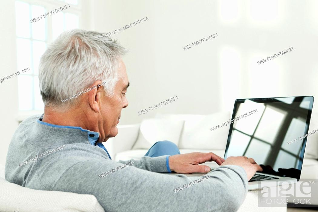 Stock Photo: Germany, Berlin, Senior man using laptop.