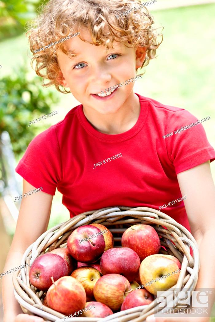 Stock Photo: Boy holding basket of apples.
