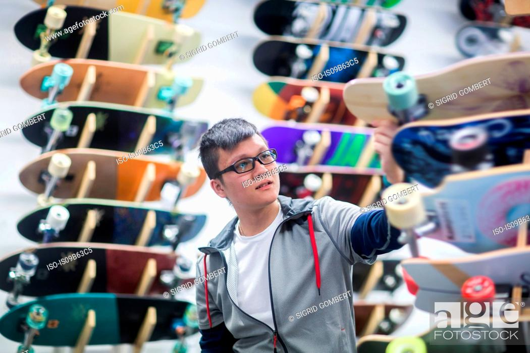 Stock Photo: Young male skateboarder looking at skateboards in skateboard shop.