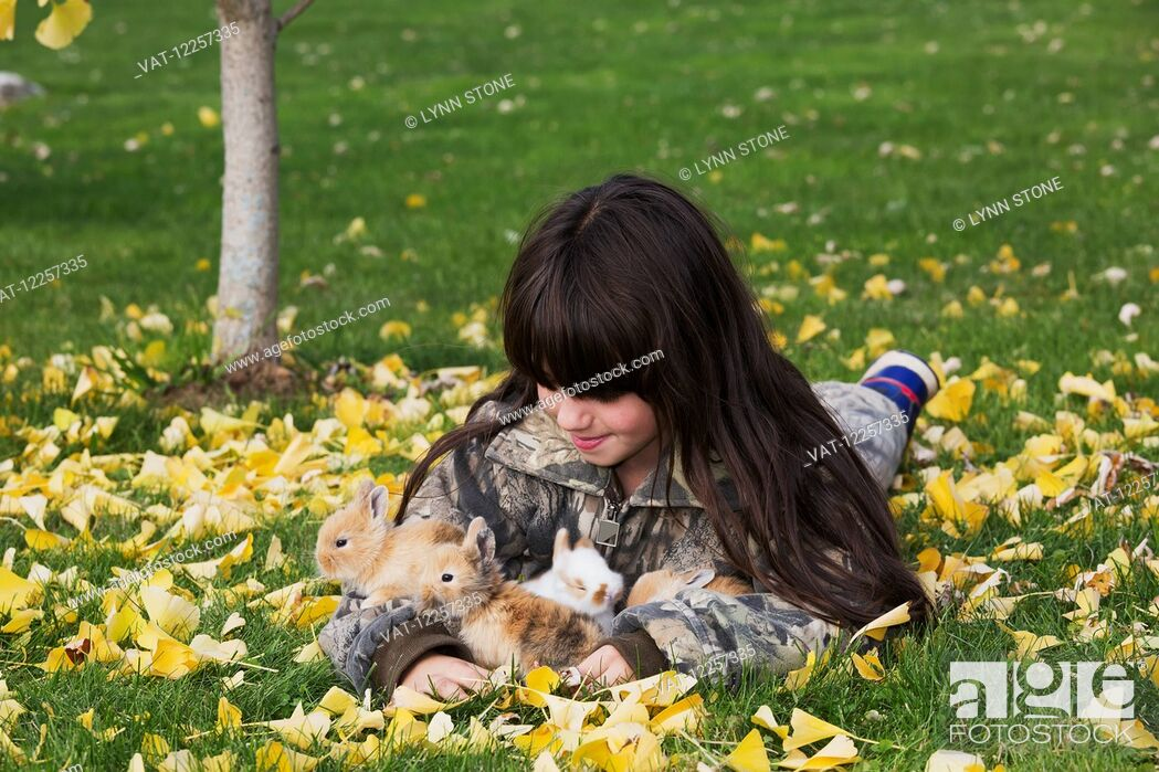 Imagen: Young girl with mixed-breed rabbit babies; Higganum, Connecticut, United States of America.