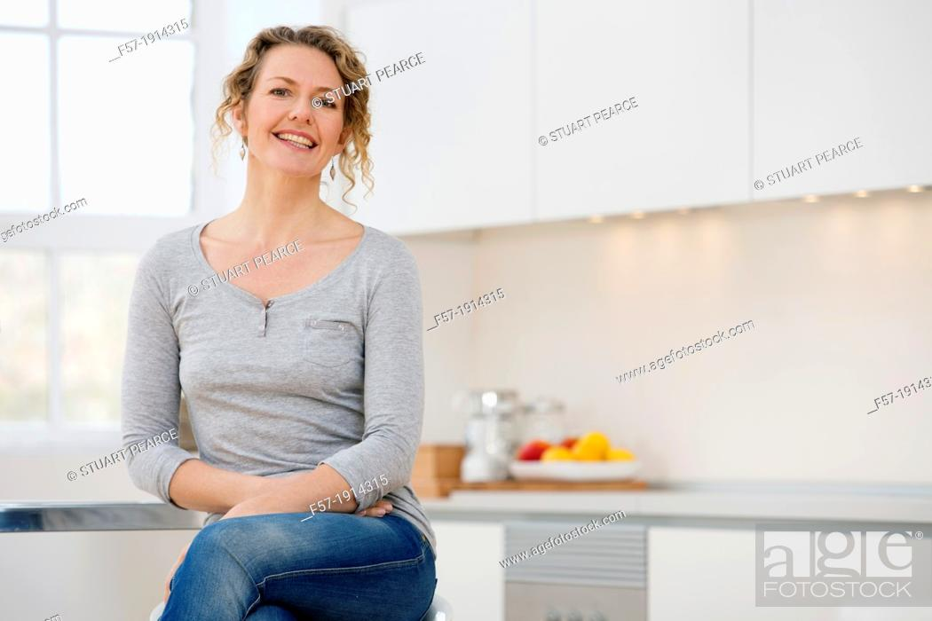 Stock Photo: Independent young woman sitting her kitchen.