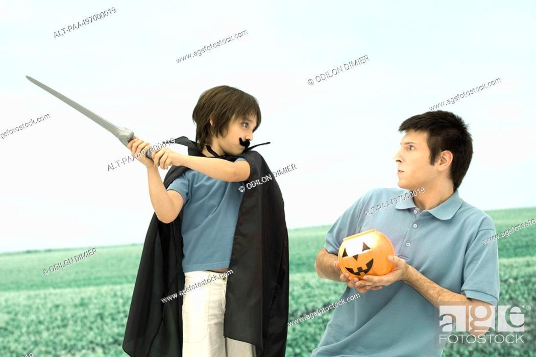 Stock Photo: Father and son playing, man holding jack o' lantern, boy swinging sword.