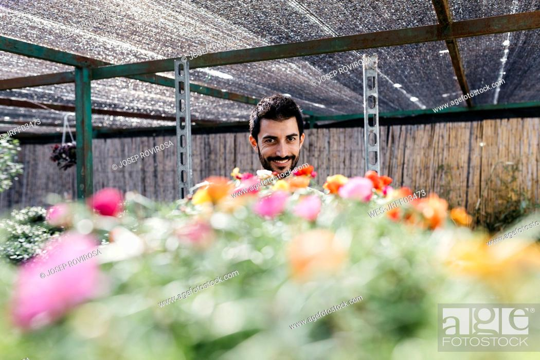 Stock Photo: Portrait of a smiling gardener in a greenhouse with flowers.