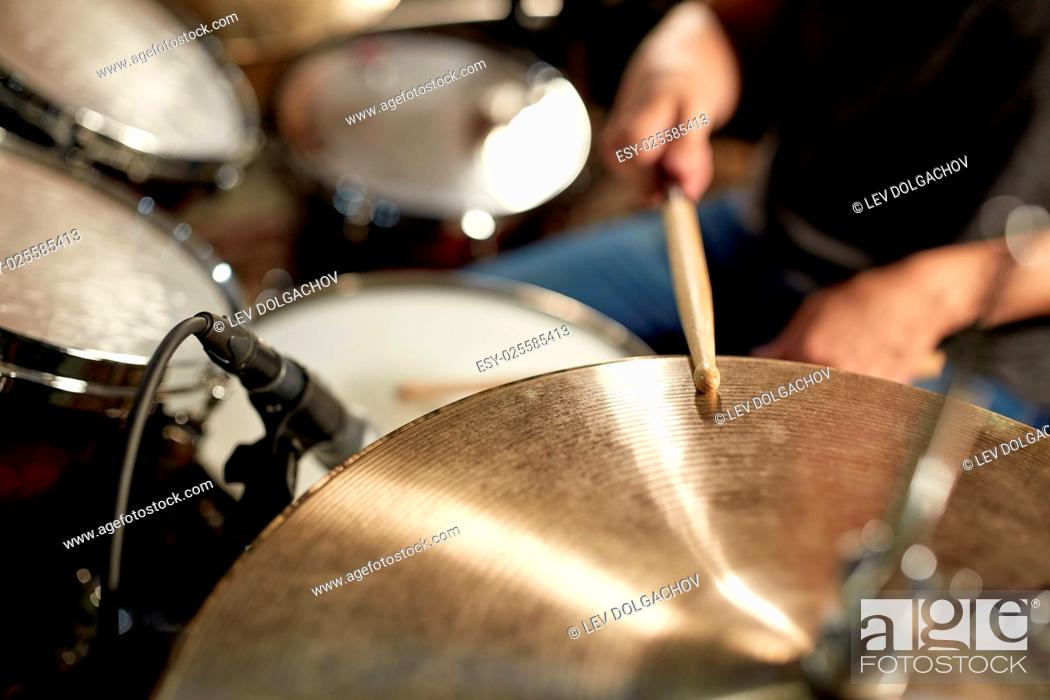 Imagen: music, people, musical instruments and entertainment concept - male musician playing drums and cymbals at concert or studio.