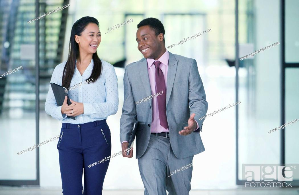 Stock Photo: Smiling business people walking and talking.