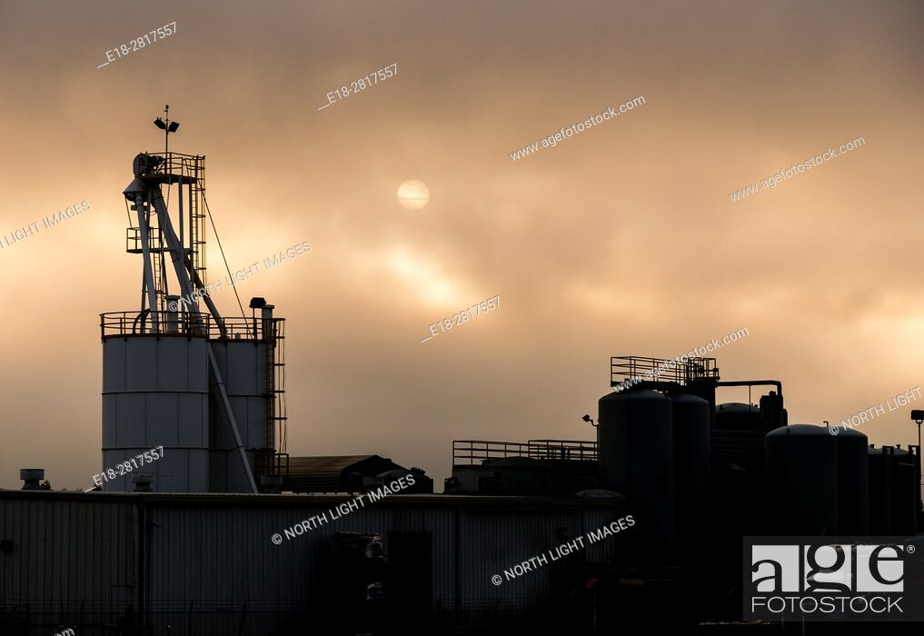 Stock Photo: USA, California. Industrial building silhouetted against orange clouds and setting sun.