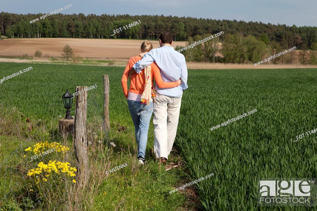 Stock Photo: A couple walking side by side in a field, rear view.