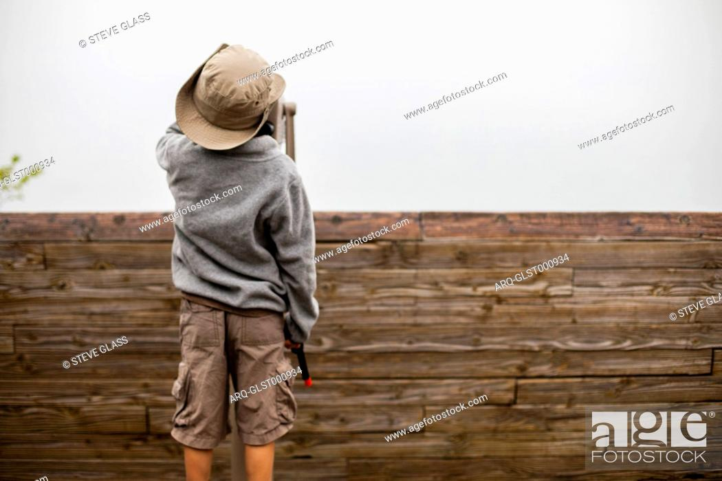 Stock Photo: A 6 year old Japanese American boy looks out of a Telescope toward Miner's Castle, along the Pictured Rocks National Lakeshore of one of the Great Lakes.