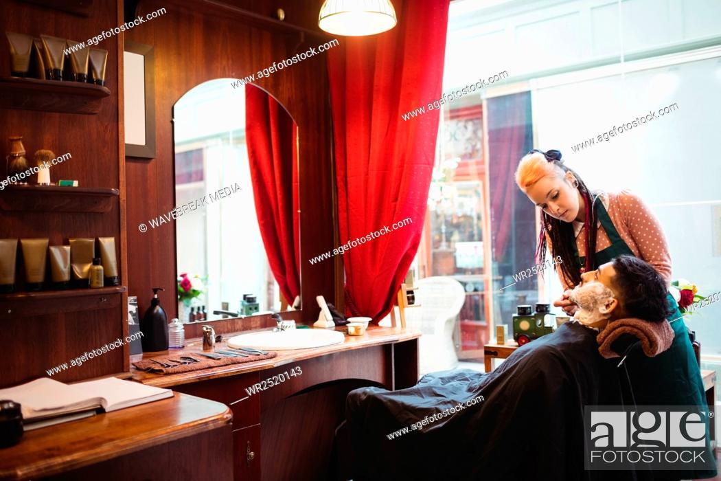 Stock Photo: Man getting his beard shaved with shaving brush.