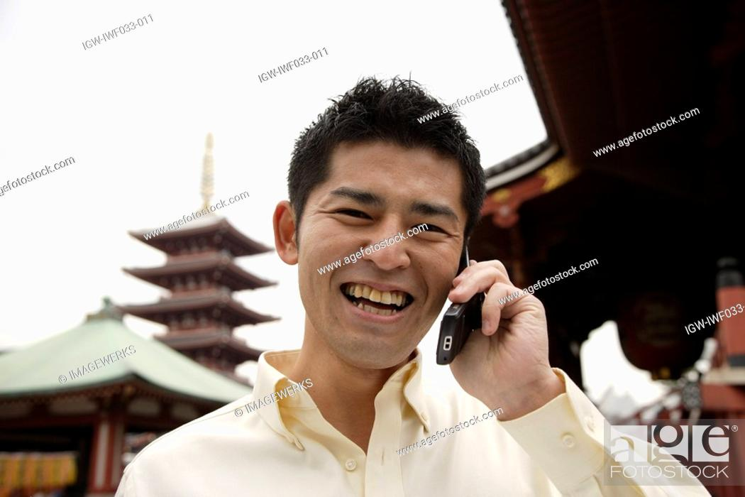 Stock Photo: A smiling young man using cellphone.