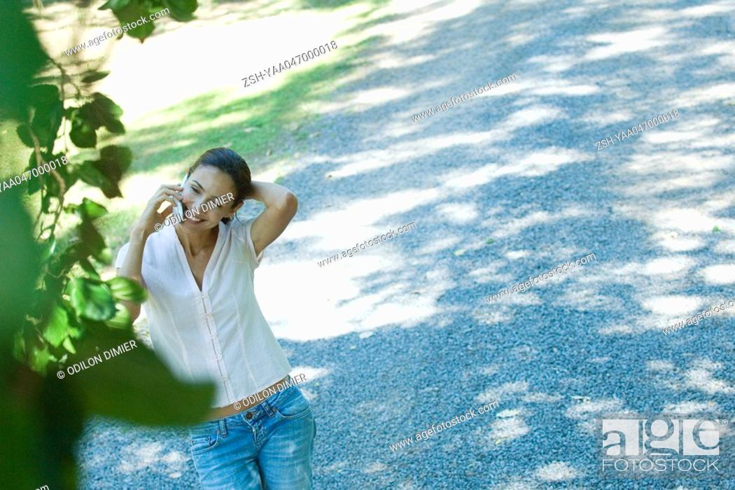 Stock Photo: Casually dressed woman using cell phone outdoors, hand behind head, high angle view.