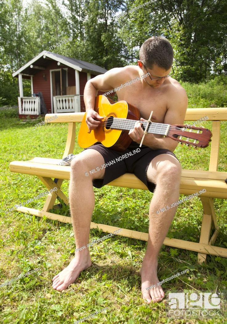 Stock Photo: Young man playing guitar on holiday.