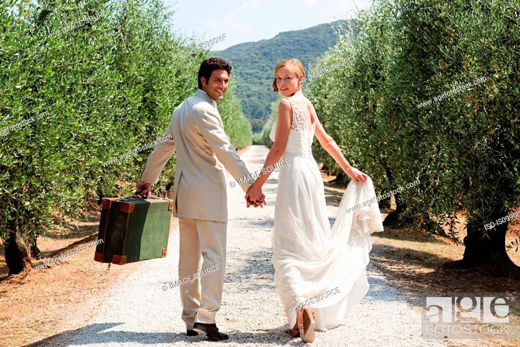 Stock Photo: Newlyweds walking on country road with suitcase.
