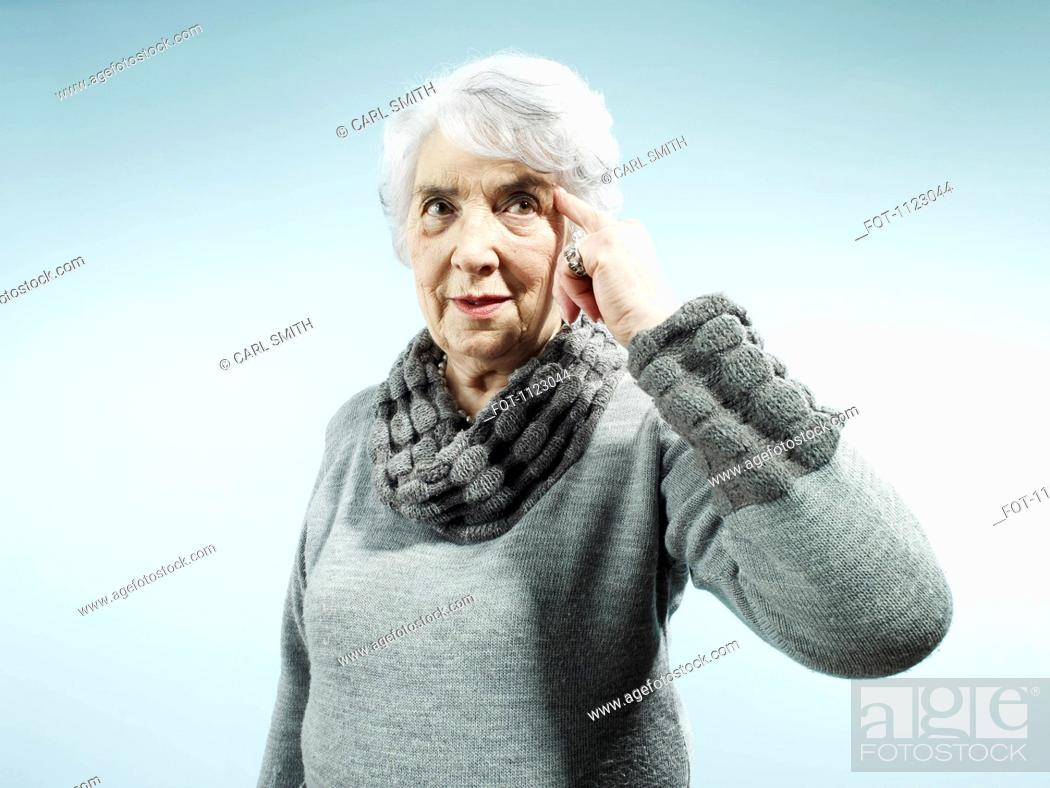 Stock Photo: A serious senior woman pointing to her temple.