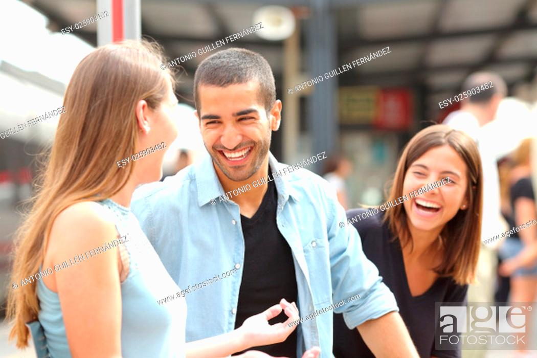 Stock Photo: Three friends talking and laughing taking a conversation in a train station.