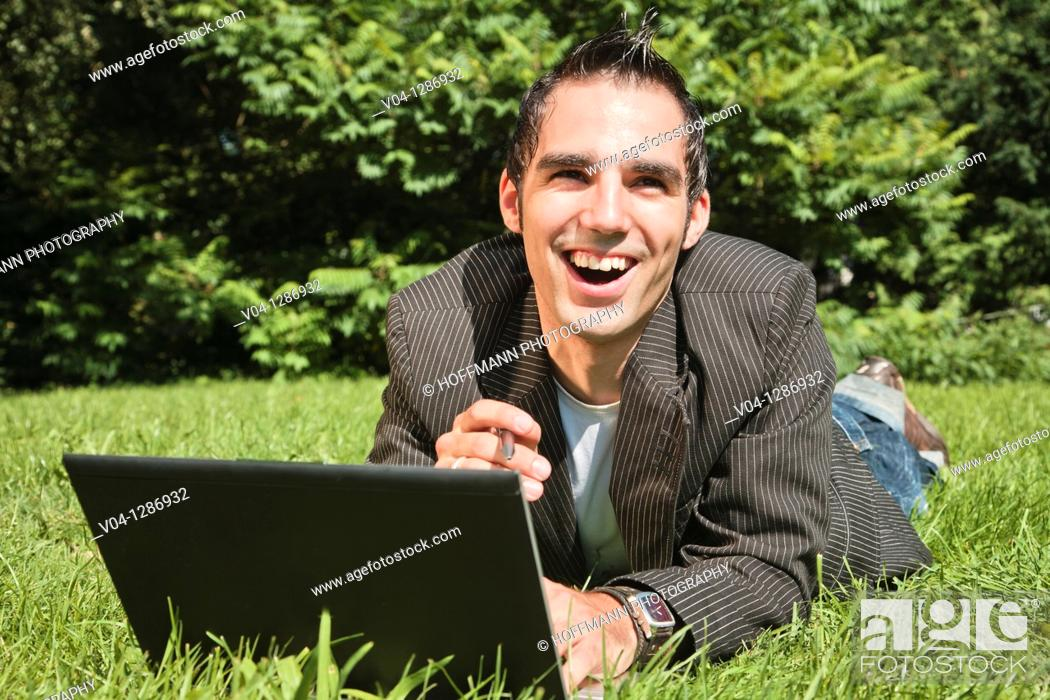 Stock Photo: Young man working outdoors on his laptop, smiling at the camera.