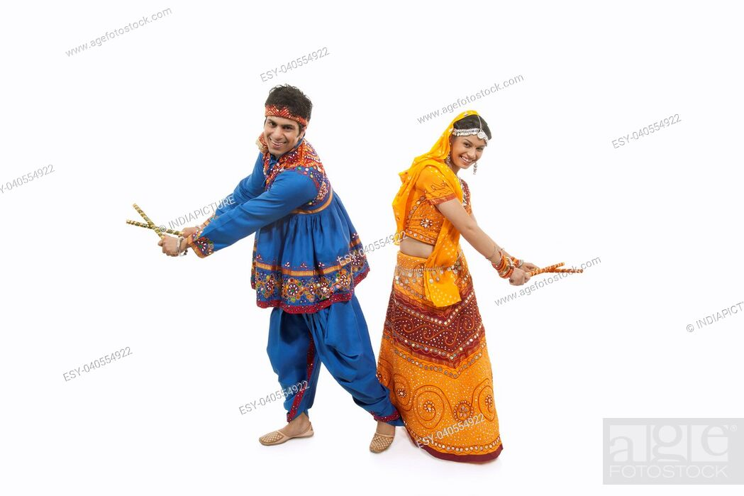 Imagen: Full length of an Indian couple in traditional wear performing Dandiya Raas over white background.