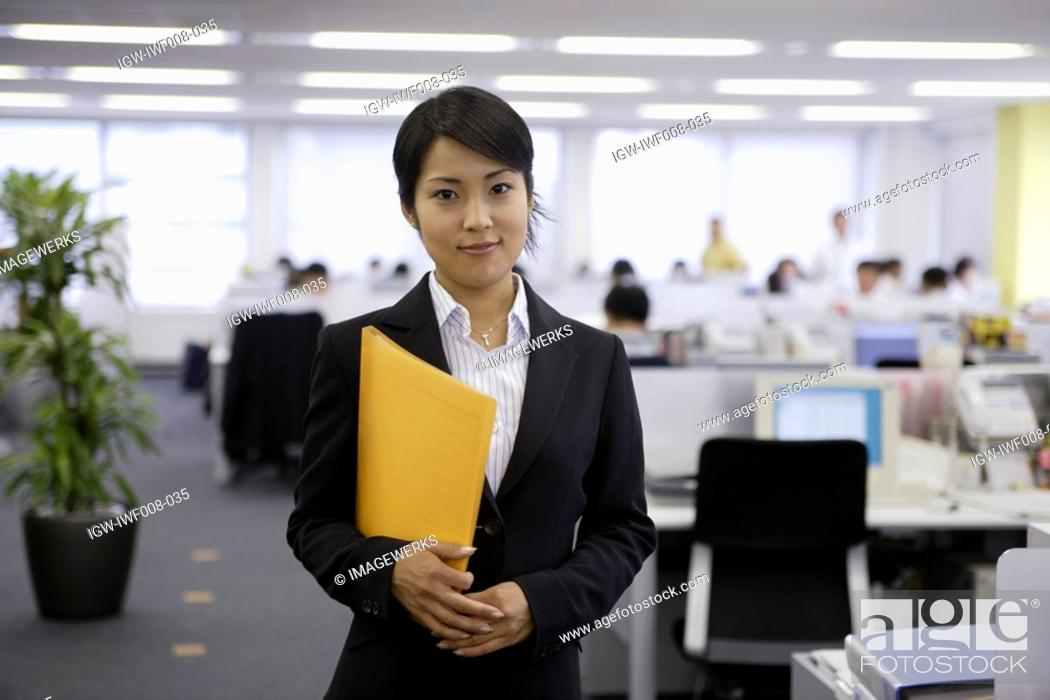 Stock Photo: A professional woman holding a file smiles at the camera in the office.
