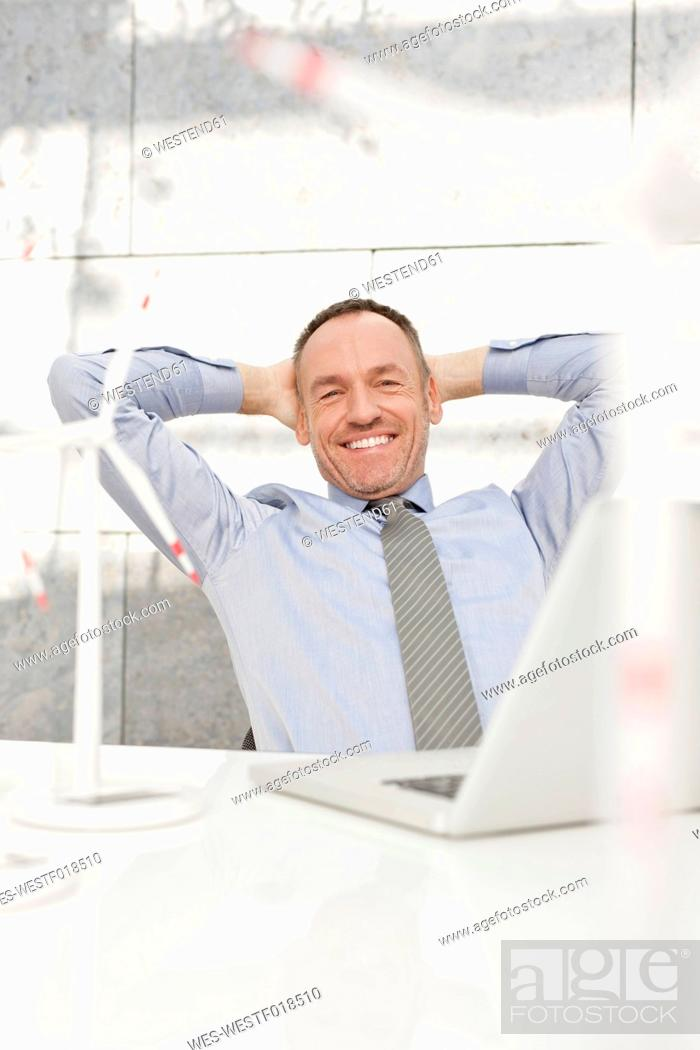 Stock Photo: Germany, Leipzig, Businessman with laptop and wind power model.