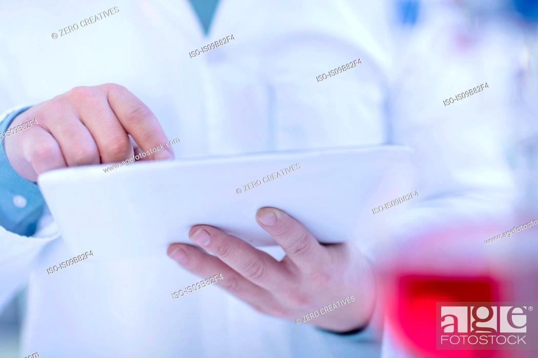 Imagen: Laboratory worker using digital tablet, mid section.