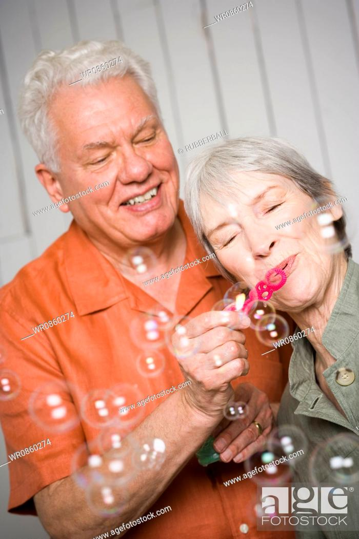 Stock Photo: Close-up of an elderly couple blowing bubbles with a bubble wand.