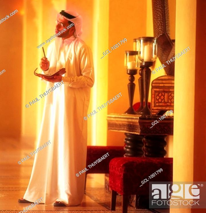 Stock Photo: Arab man holding a filofax and a pen.
