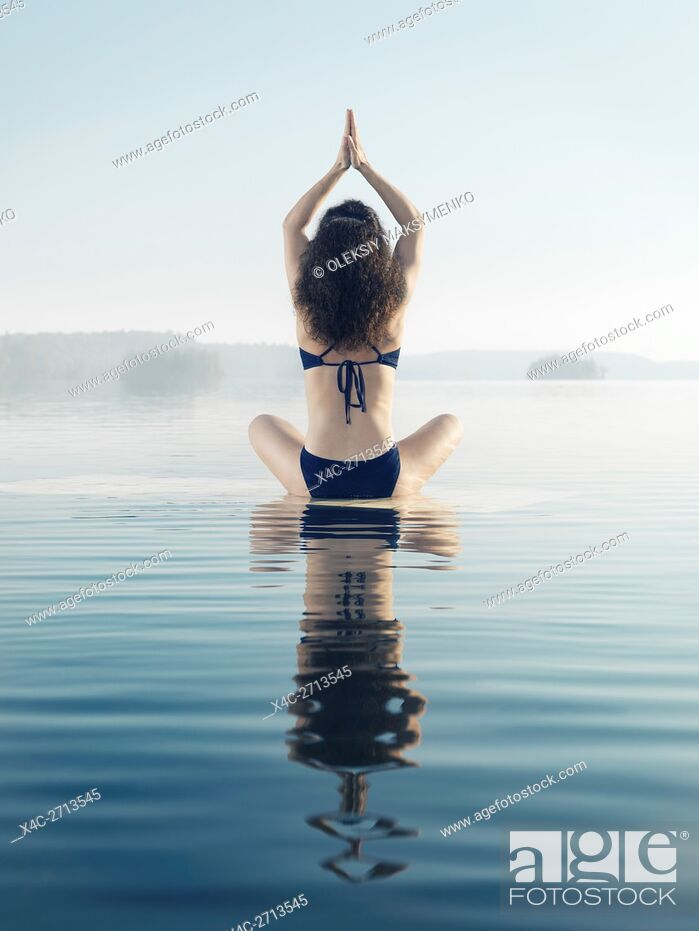Stock Photo: Artistic photo of a woman meditating on a platform in calm water on a misty lake in early morning during sunrise. Yoga meditation. Rear view.