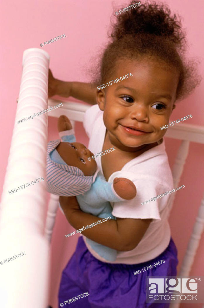 Stock Photo: High angle view of a baby girl holding a doll.