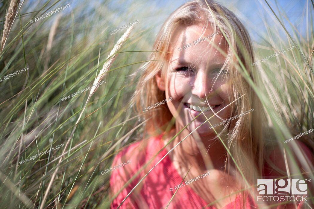 Stock Photo: Portrait of blonde woman in marram grass, Wales, UK.