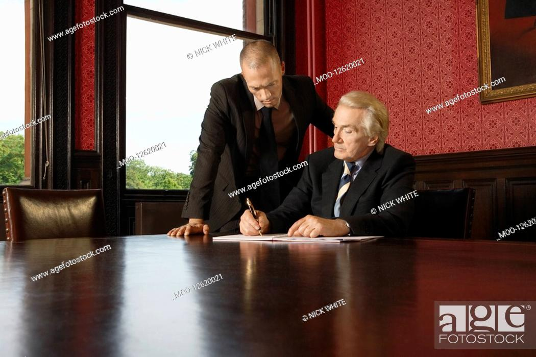 Stock Photo: Two Men in Conference Room one leaning over other.