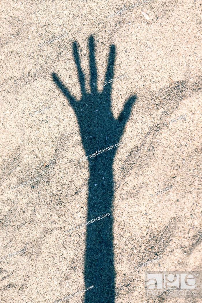 Stock Photo: Shadow of hand over sand background.