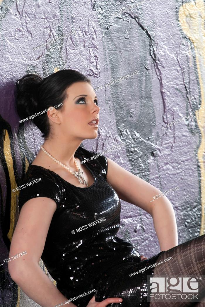 Stock Photo: A fashion model in front of a wall covered with graffiti.