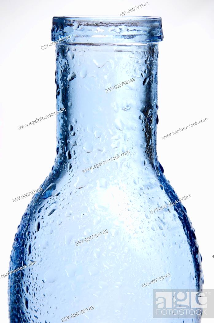 Stock Photo: foreground of a blue glass bottle with splashes of water and white background.